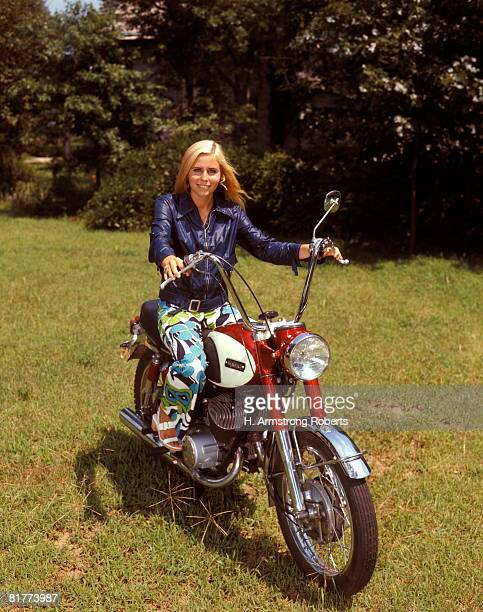 Smiling blonde woman sitting on red motorcycle.