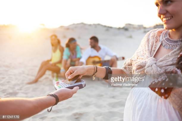 Sonriente mujer boho con tarjeta de crédito en la playa