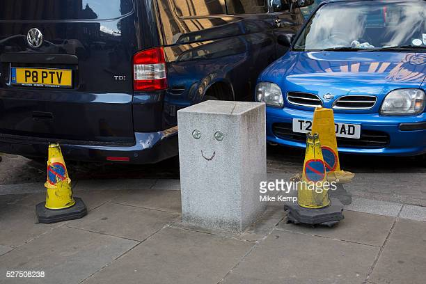 Smiling bollard and police cones at a parking bay in London UK