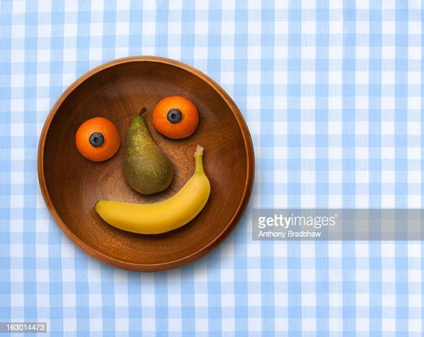 Smiling bowl of fruit on gingham