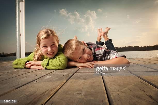 Lächelnden Jungen und Mädchen auf dem Bauch liegen pier am lake