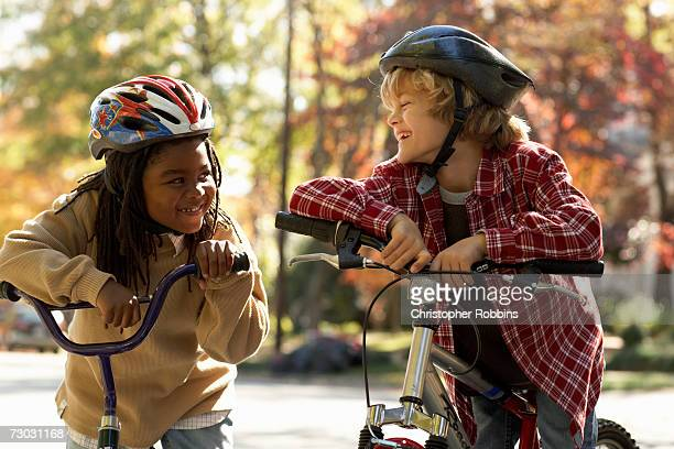 Smiling boy (8-9) and girl (6-7) standing at bicycle in park, smiling