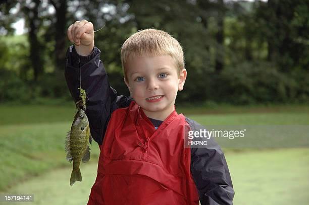 Souriant garçon captures de poissons en étang premier