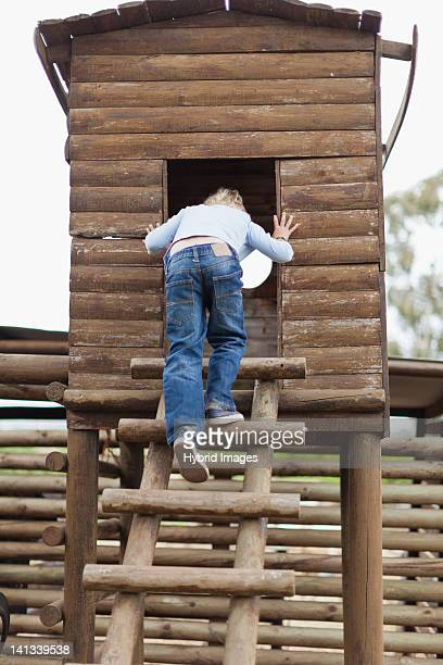 Smiling boy climbing into playhouse