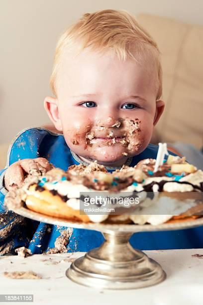 Souriant garçon mange un gâteau Grand