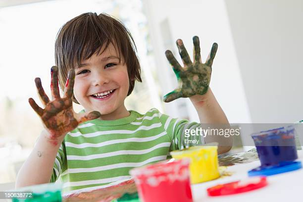 Smiling boy finger painting indoors
