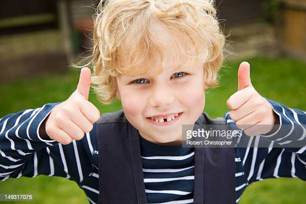 Smiling boy giving thumbs-up outdoors