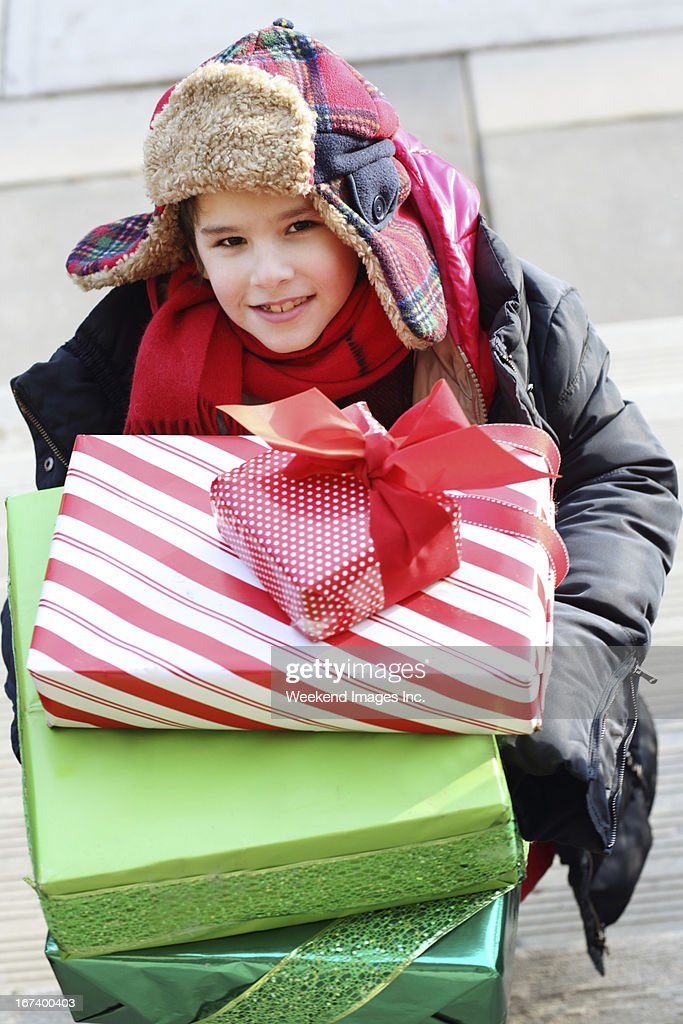 Smiling boy hold the stack of gift boxes : Stock Photo