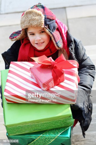 Smiling boy hold the stack of gift boxes : Stockfoto