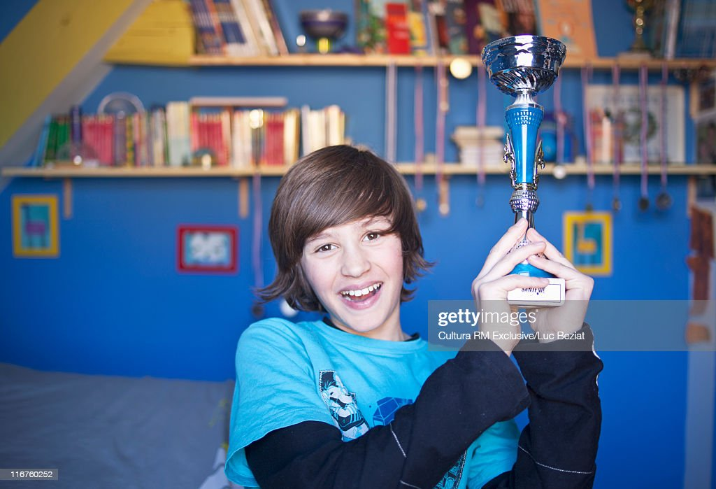 Smiling boy holding trophy in bedroom : Stock Photo
