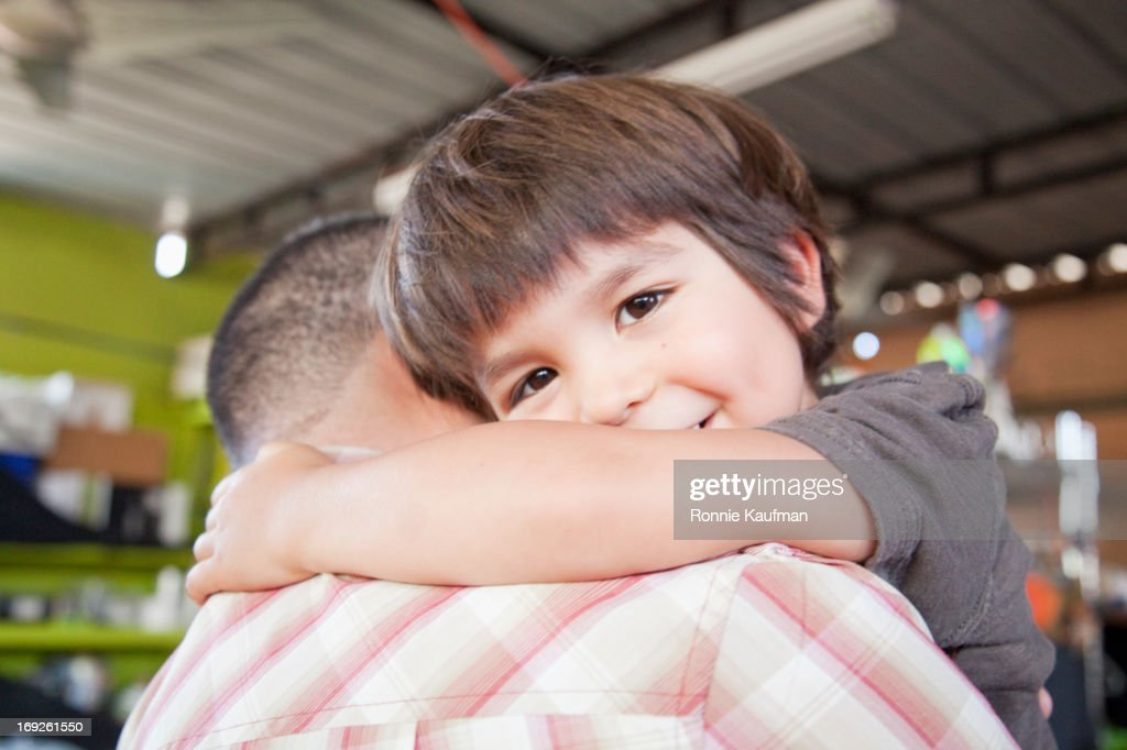 Smiling boy hugging father : Stock Photo