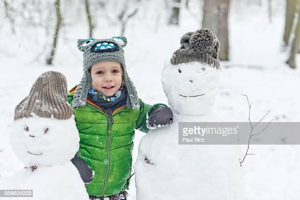 Smiling boy hugging snowman