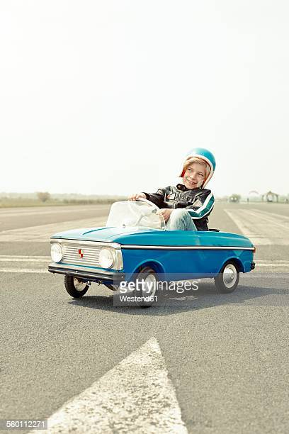 Smiling boy in pedal car on race track