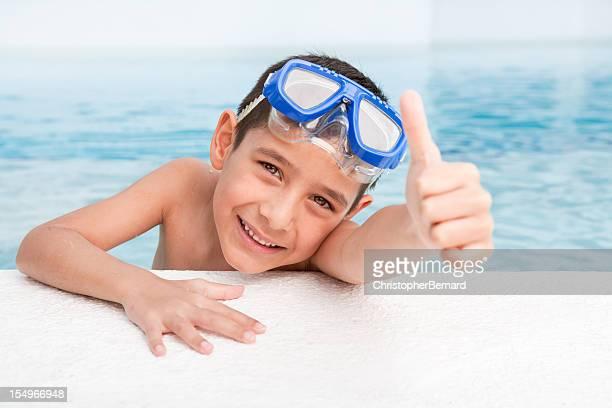 Sorridente ragazzo in piscina con pollice in alto