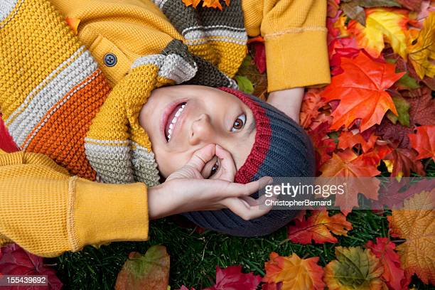 Smiling boy laying on autumn leaves