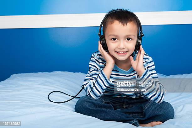 Smiling boy listening to headphone in bed