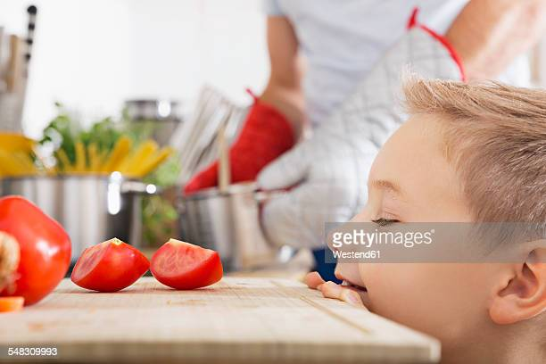 Smiling boy looking at tomato slices on kitchen board