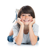 Closeup of smiling little boy with freckles lying on white background. Happy cute male child lying on white floor and looking at camera. Portrait of a smart young boy. Adorable caucasian kid lying wit
