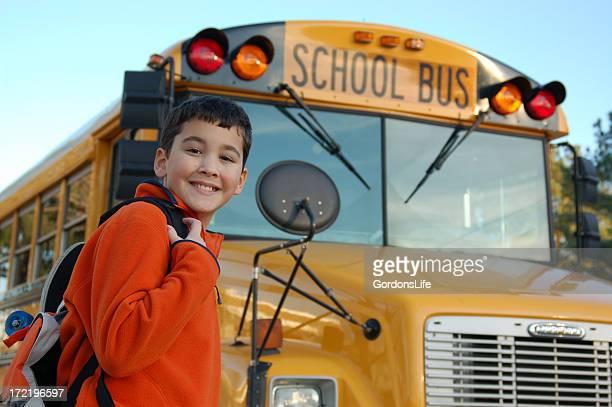 Smiling boy near the school bus