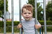 Smiling boy in park on fence background