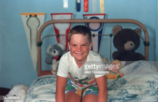 Smiling boy on his bed in his bedroom : Stock Photo