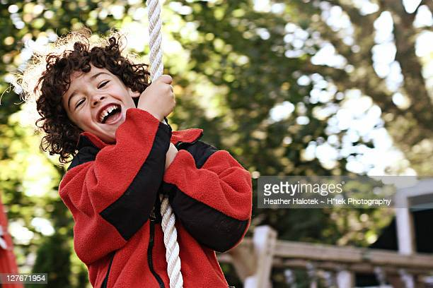 Smiling boy on zip line swing