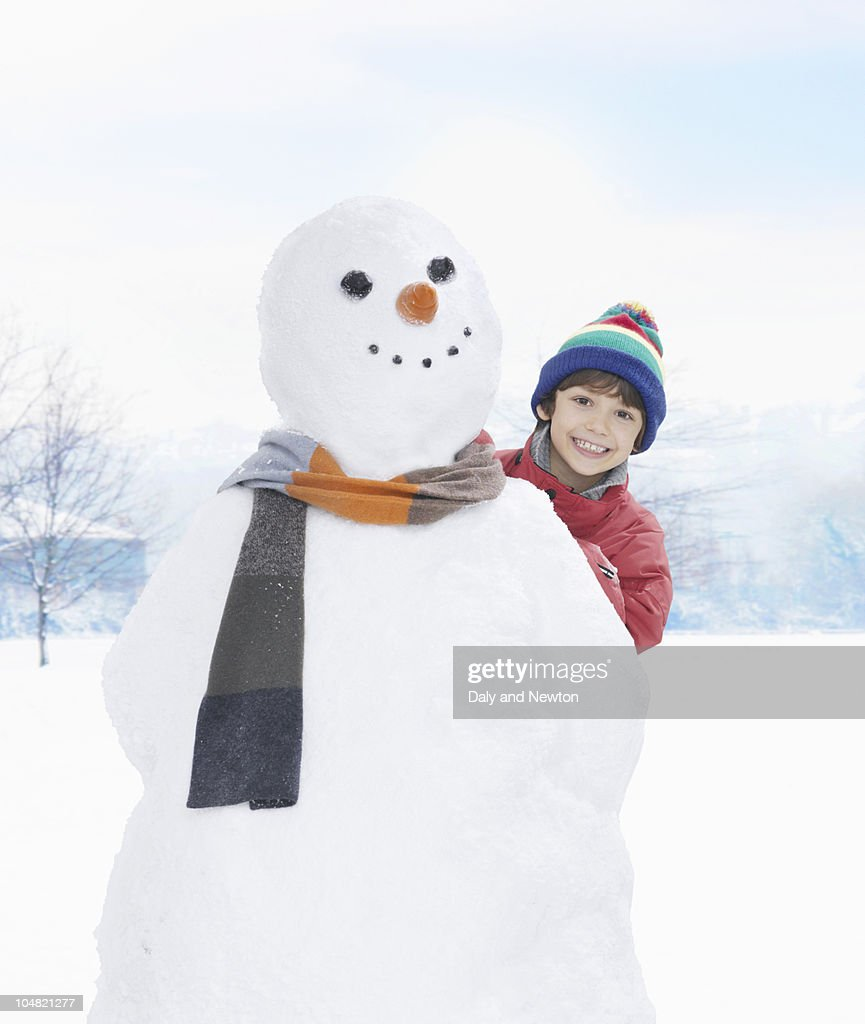 Smiling boy peering from behind snowman : Stock Photo