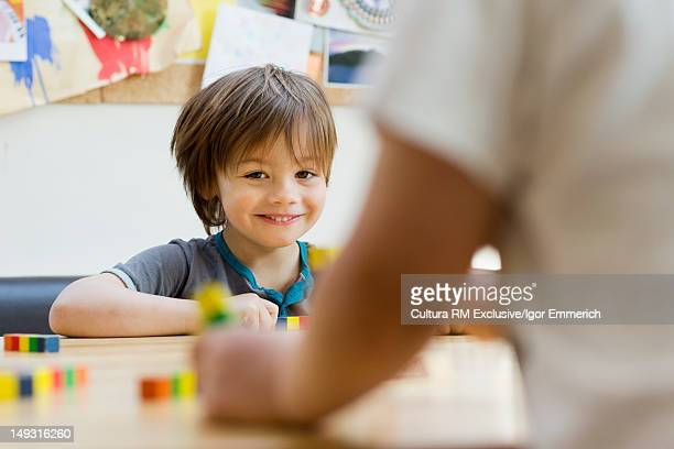 Smiling boy playing with blocks at table