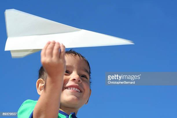 Smiling boy playing with paper airplane