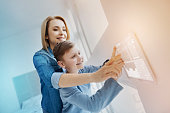 Funny device. Cheerful emotional boy feeling excited while his kind mother helping his to use a modern device on the wall