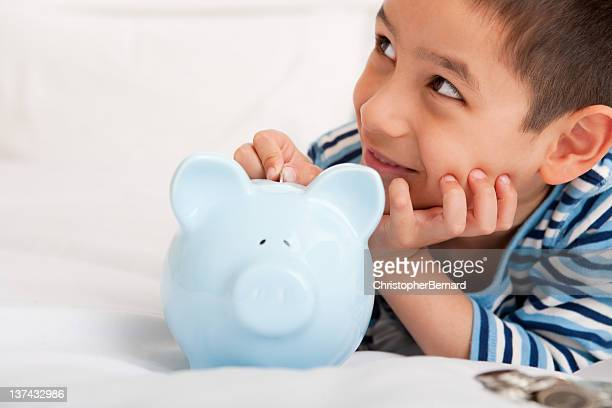 Smiling boy putting money in piggy bank