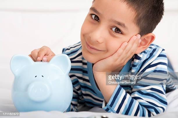Smiling boy putting money in piggy bank
