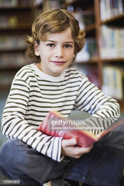 Smiling boy reading in library
