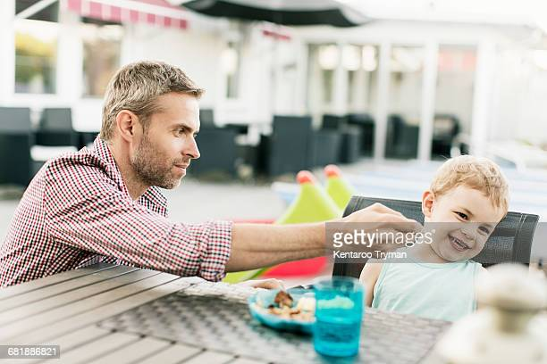 Smiling boy refusing to eat food offered by father at restaurant