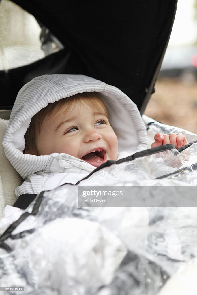 Smiling boy riding in stroller outdoors