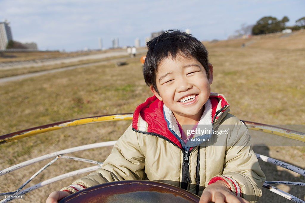 Smiling boy riding on the playground equipment. : Stock Photo