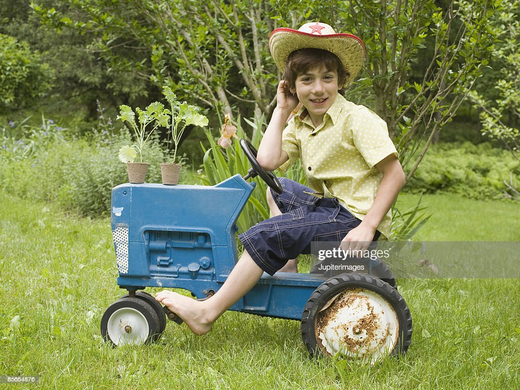 Boy On Tractor : Smiling boy riding tractor stock photo getty images