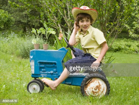 Smiling boy riding tractor