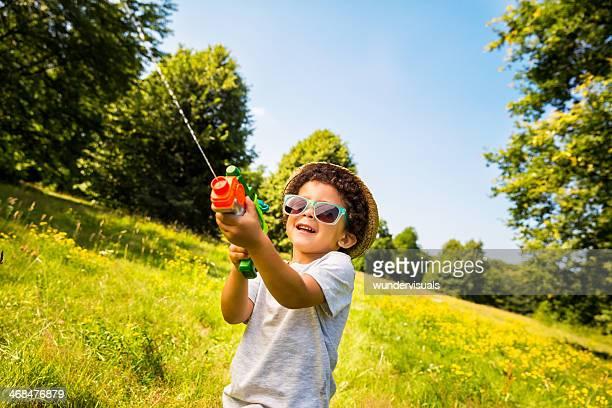 Menino sorridente de água com pistola de água