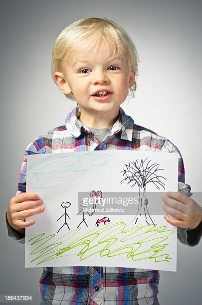 Smiling boy showing off his drawing