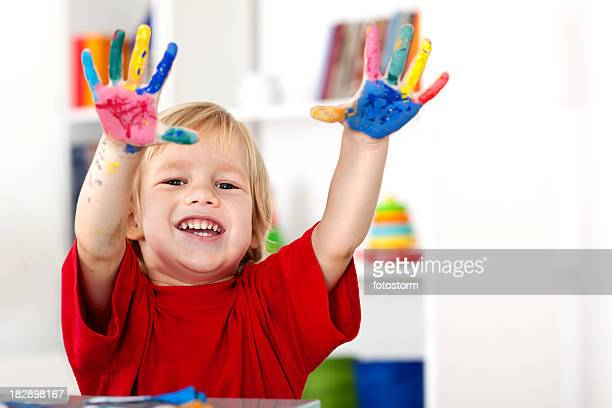 Smiling boy showing painted hands