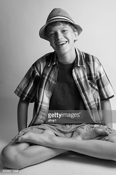 Young boy (12-13) laughing while sitting crosslegged and wearing hat