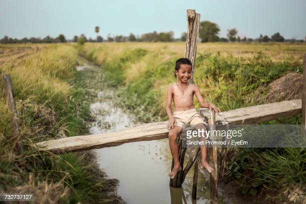 Smiling Boy Sitting On Wood Over Canal At Farm
