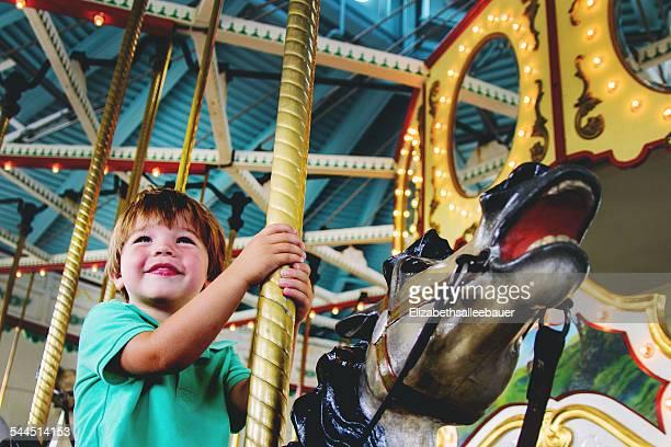 Smiling boy (2-3) smiling on carousel