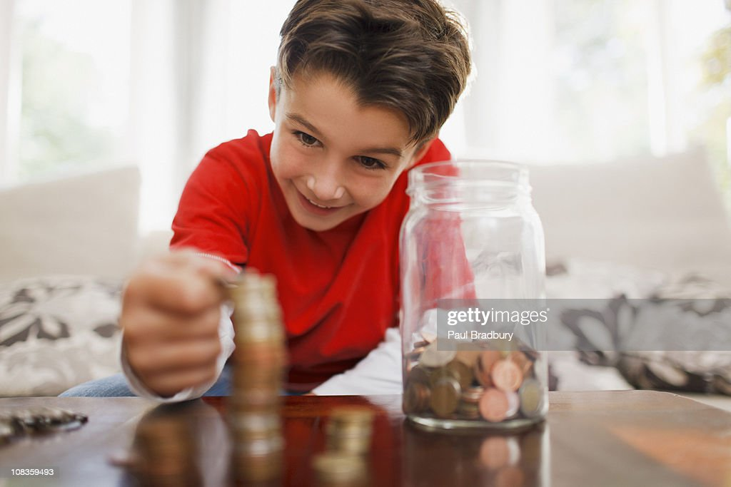 Smiling boy stacking coins : Stock Photo