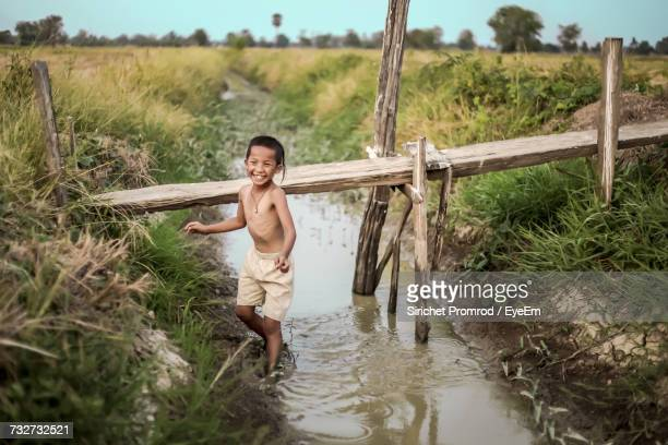 Smiling Boy Standing On Canal At Farm Against Sky
