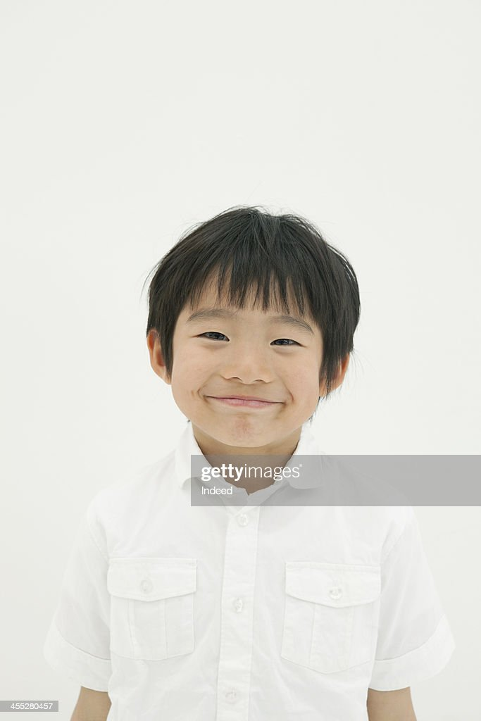 Smiling boy stands in front of the white background