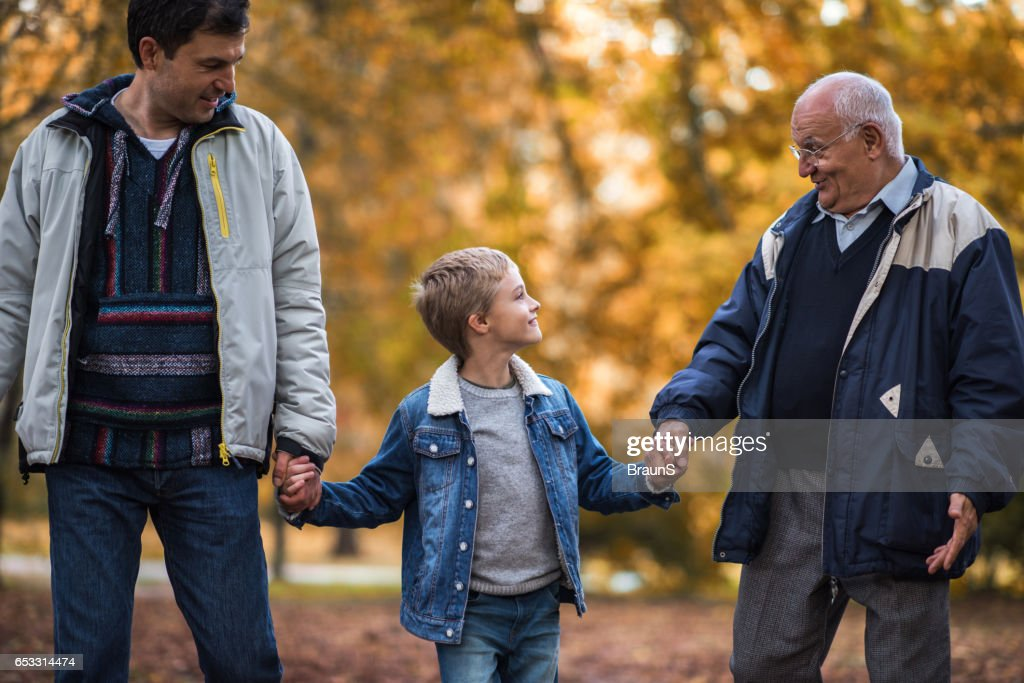 Smiling boy talking to his grandpa and father in nature. : Photo
