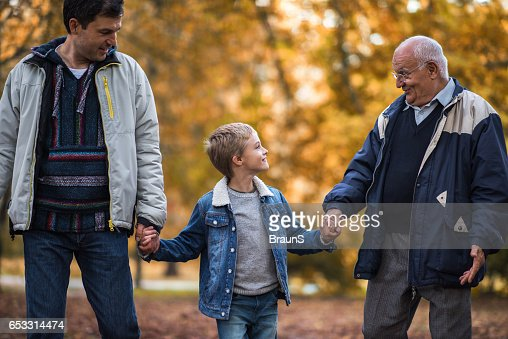 Smiling boy talking to his grandpa and father in nature. : Stock Photo