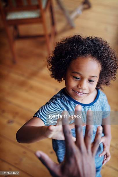 Smiling boy touching father's hand at home